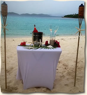 Tiki torches accenting rum punch set up at Lindquist Beach wedding